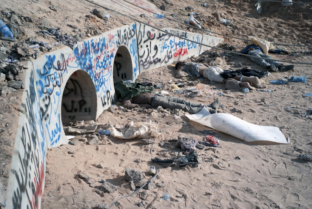 Bodies of killed gaddafi loyalists around the drain pipe where the