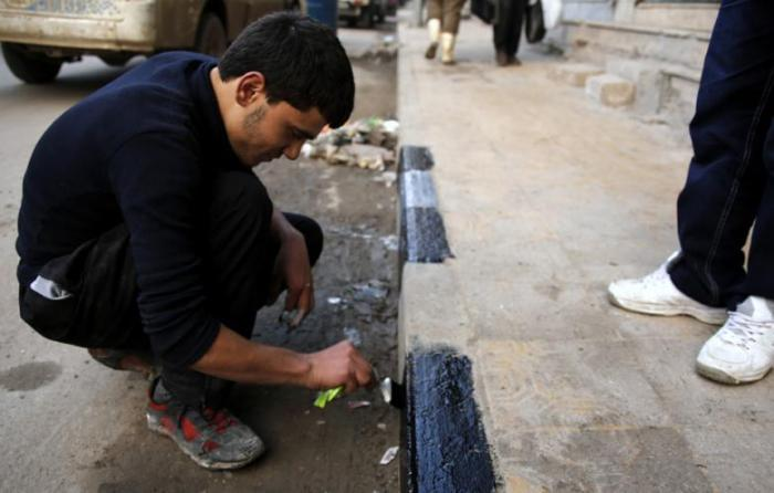 A Syrian man paints stripes on a side walk the northern Aleppo province, on 16 December 2012. (Photo: AFP - Prashant Rao)