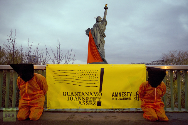 (Amnesty International activists, dressed in orange jumpsuits similar to those worn by prisoners at the US detention camp in Guantanamo Bay AFP Photo / Joel Saget)