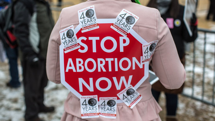 An anti-abortion protester has a sign stuck to her back with stickers at the March for Life on January 25, 2013 in Washington, DC (Brendan Hoffman/Getty Images/AFP)