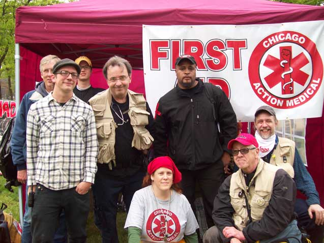 "May 1, 2012: ""Danny Edwards"" - posing with fellow Chicago Action Medical volunteers at their health care booth in Union Park, where street medics were volunteering to provide first aid and emergency health care for participants at the annual May Day rally and march. ""Danny"" - the only medic not smiling - is standing in front of the CAM banner."
