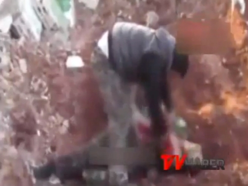 Syrian rebel warlord Abu Sakkar, founder of the Farouq Brigade, cutting out the vital organs of a dead soldier.