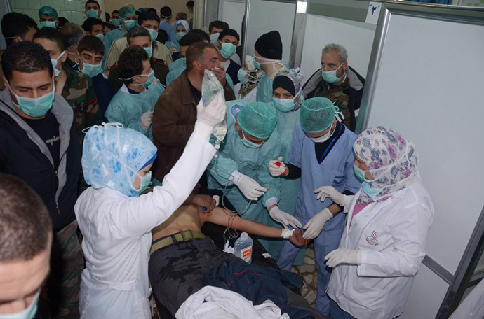 In this image made available by the Syrian News Agency (SANA) on March 19, 2013, medics and other masked people attend to a man at a hospital in Khan al-Assal in the northern Aleppo province, as Syria's government accused rebel forces of using chemical weapons for the first time. (AFP Photo / SANA)