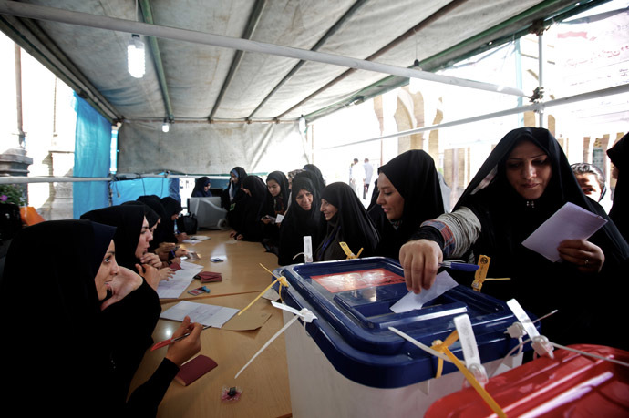 Female Iranian election officials check the IDs of the women voters as they cast their ballots during the first round of the presidential election at a polling station in Shah Abdolazim mausoleum, in southern Tehran, on June 14, 2013. (AFP Photo)