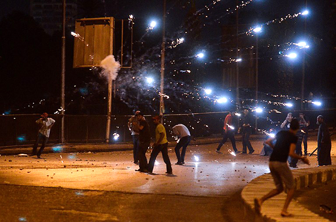 Ousted president Mohamed Morsi supporters and anti Morsi protesters hurl stones at each other as they clash near Egypt's landmark Tahrir square on July 5, 2013 in Cairo. (AFP Photo / Mohamed El-Shahed)