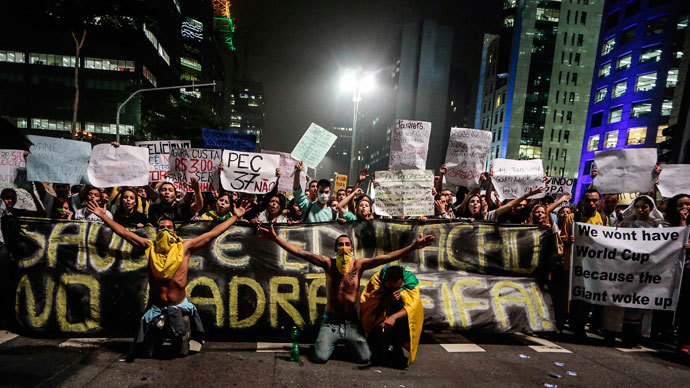 Demonstrators hold a banner demanding an improvement for education and health in Sao Paulo, Brazil, on June 20, 2013.(AFP Photo / Miguel Schincariol)