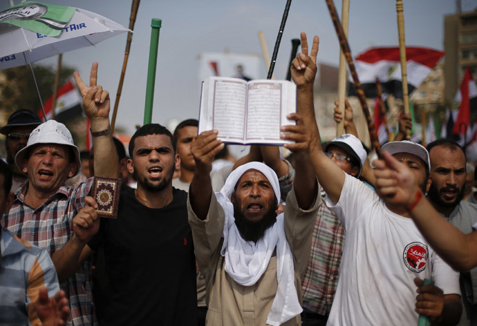 Supporters of Egyptian President Mohamed Morsi hold copies of the Koran during a protest around the Raba El-Adwyia mosque square in Nasr City, in the suburb of Cairo June 30, 2013. (Reuters)
