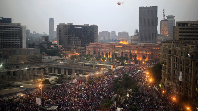 An Egyptian army helicopter flies over protesters calling for the ouster of President Mohamed Morsi in Cairo's landmark Tahrir Square on July 3, 2013 (AFP Photo / Gianluigi Guercia)