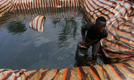 A man collects crude oil for an illegal refinery in Nigeria's Bayelsa state, 2012. The resource drain is holding Africa back, says the AfDB. Photograph: Akintunde Akinleye/Reuters