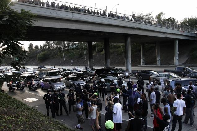 Demonstrators block traffic Sunday on the freeway in Los Angeles as police in riot gear stand at the ready.