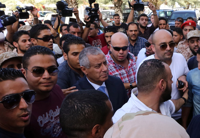 Libyan Prime Minister Ali Zeidan (C) arrives at the government headquarters in Tripoli on October 10, 2013 shortly after he was freed from the captivity of militiamen who had held him for several hours (AFP Photo / Mahmud Turkia)