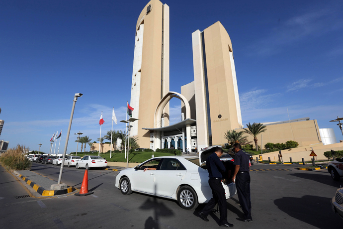 A general view taken on October 10, 2013 shows security checking a vehicle outside the Corinthia hotel (background) in the Libyan capital Tripoli after Libyan Prime Minister Ali Zeidan was kidnapped from the hotel (AFP Photo / Mahmud Turkia)