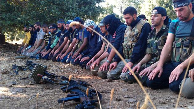 Members of the Free Syrian Army perform prayers in Damascus in August 13, 2012. UPI