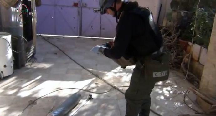 An image grab taken from a video uploaded on YouTube by Moadamiyet al-Sham media centre on August 26, 2013 allegedly shows a United Nations (UN) arms expert measuring and photographing a canister in Damascus' Moadamiyet al-Sham suburb as they investigate an alleged chemical weapons strike in the capital (AFP Photo)
