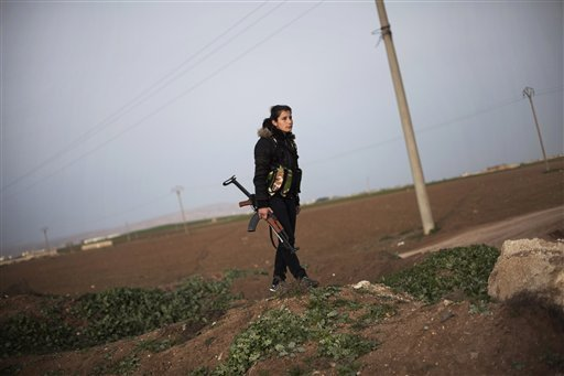 FILE - In this Sunday, March. 3, 2013 file photo, A Kurdish female member of the Popular Protection Units stands guard at a check point near the northeastern city of Qamishli, Syria.