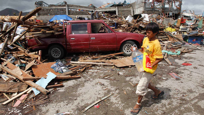 A boy carrying a plastic bottle of water walks past a car which slammed into damaged houses after super Typhoon Haiyan battered Tacloban city, central Philippines November 10, 2013.(Reuters / Romeo Ranoco)