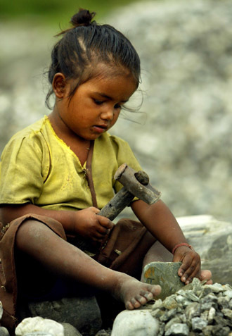 Five-year-old Rina breaks stones in Siliguri in this picture taken September 2, 2004. Rina has been a professional rock breaker for a year, slaving six days a week in the sapping heat and humidity of West Bengal. (Reuters/Kamal Kishore)