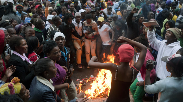 RODGER BOSCH/AFP/Getty Images People taking part in a protest agaianst poor public services sing and dance around a rubbish fire on October 30, 2013, in the centre of Cape Town. The people congregated outside the Western Cape provincial Legislature, calling for Western Cape Premier(not visible) to come and address them.