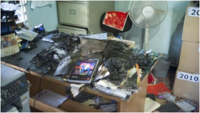 Documents damaged by fire are seen on a desk in an office of the Probusqueda Association for Missing Children in San Salvador