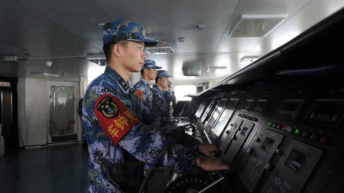 Chinese naval soldiers are pictured manning their stations on China's first aircraft carrier Liaoning, as it travels towards a military base in Sanya, Hainan province, in this undated picture made available on November 30, 2013. (Reuters / Stringer)